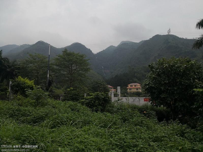 一片绿色中的山间别墅,远处是巍峨的飞霞山脉