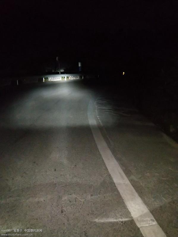 右转弯道远光灯效果,弯道前方护栏可见,凸字形灯光使弯道右侧一片漆黑